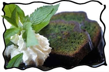 Green mint chocolate cake slices with whipped cream and fresh mint leaves