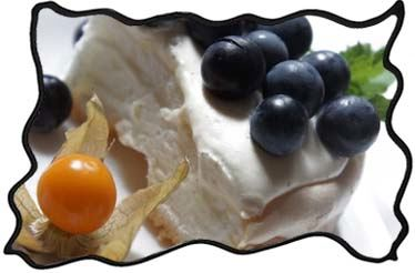 Slice of Pavlova cake with grapes and physalis